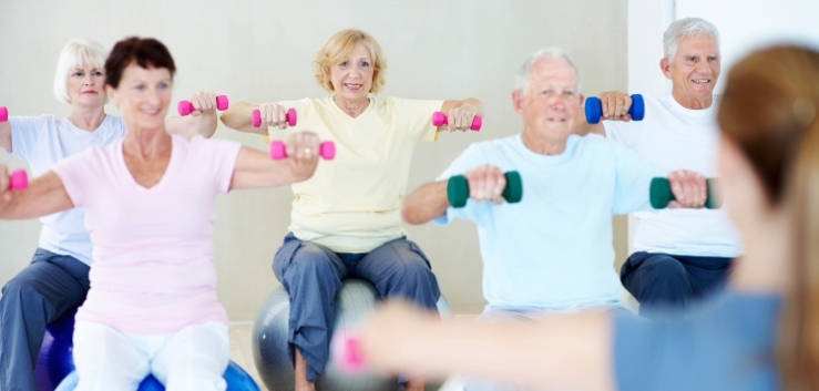 A group of elderly people lifting weights together in a fitness class